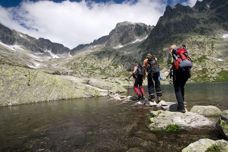 backpackers: Group of people crossing mountain pond in Tatra Mountains, Slovakia