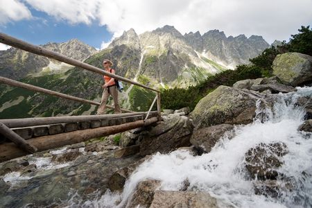 Young women walking through footbridge in High Tatra Mountains, Slovakia Stock Photo