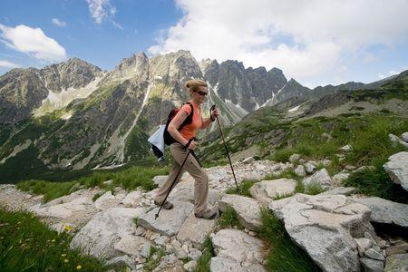 Female is trekking in Tatra Mountains. Trail to Rysy peak photo
