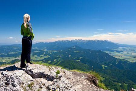 Girl on the top of Velky Chocz in Slovakia. Tatras Mountains far away.