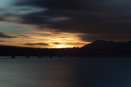 Nice sunset after a viaduct crossing over a lake Archivio Fotografico