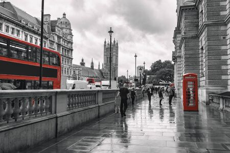 Traditional red buses running through westminster surrounded by tourists and old red telephone booths in the city of London