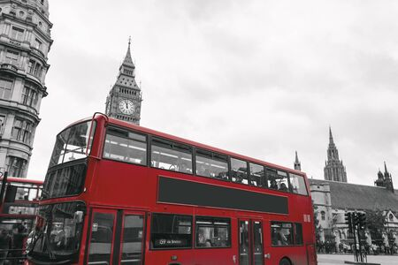 Classic red double-decker British bus, circulating through the center of the city of London among tourists in front of the well-known Big Ben