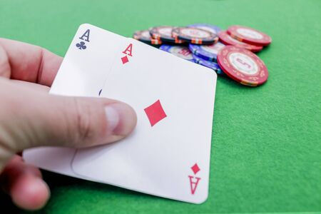 Hand holding two playing cards with aces as winning play on colored poker chips on a green game table