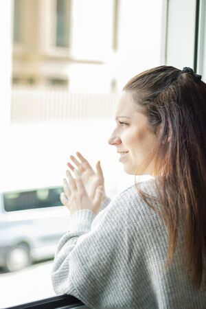 Young woman leaning out of the window applauding