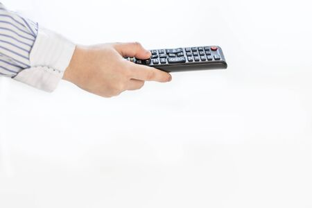 Caucasian woman's hand, holding a black multimedia television remote control, on a white background, concepts, selective focus