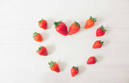 Top view of fresh strawberries on a rustic white wooden table, creating the shape of a heart, as a symbol of love. Concepts, san velentin, romantic