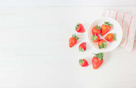 Top view of fresh strawberries on a white rustic wooden table, inside a bowl ready to eat as organic and healthy food, next to a cloth with red stripes