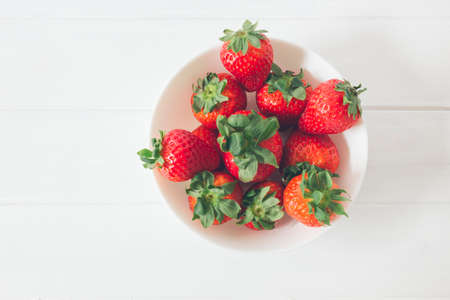 Top view of fresh strawberries on a white rustic wooden table, inside a bowl ready to eat, as organic and healthy food Foto de archivo