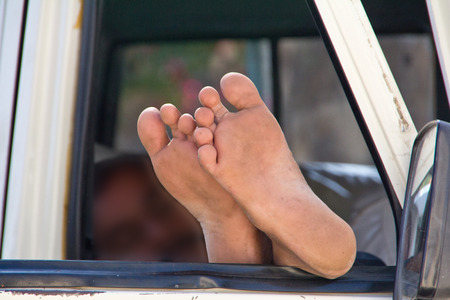 The driver sleeps legs sticking out the car window