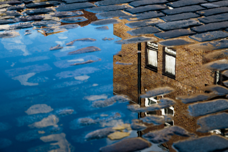 housing crisis: Cobblestone with reflection of house in puddle after rain Stock Photo