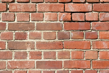 Background Of Old Red Brick Wall With Scratches Holes And Gaps Photo