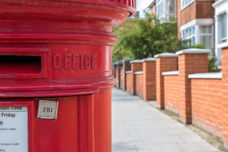 royal mail: Traditional British post box against blurry terrace house background Stock Photo