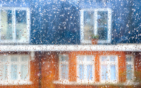 sombre: Drop of rain on window pane, blurry terrance house in background