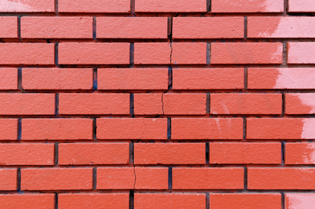 unevenly: Texture of unevenly painted red brick wall with a vertical crack