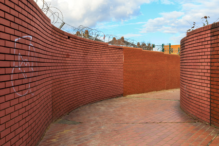 walled: Curving walled path with graffitied red brick walls topped with barbed wire Stock Photo