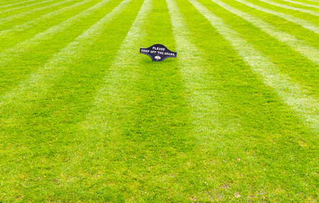green been: A beautiful green garden lawn that has just been mowed with an attractive pattern of stripes and a sign of Please Keep Off The Grass
