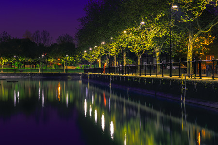 secret place: Row of lampposts and their reflection from Surrey Water in London after sunset