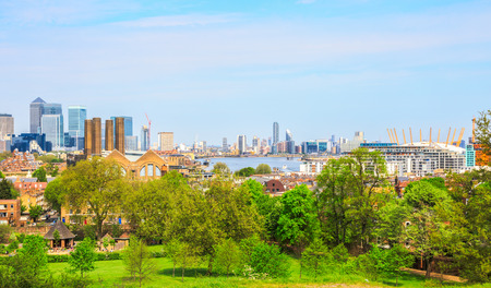 gentrification: London, UK - May 9, 2016 - Panoramic view of London cityscape from Greenwich Hill, featuring Canary Wharf, Greenwich Power Station, river Thames and the O2 Arena