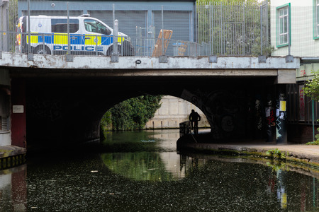 grudge: Street security metaphor: UK police vehicle and an unidentified cyclist passing under the bridge on the canal bank in London