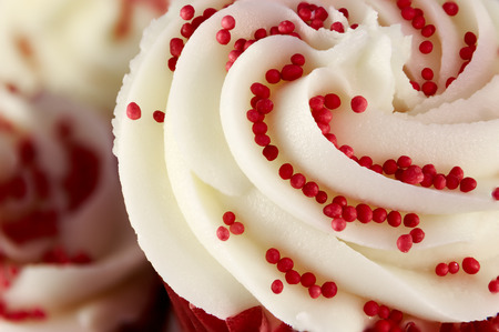 red velvet cupcake: Closeup of red velvet cupcake decorated with swirled icing and sugar beads Stock Photo