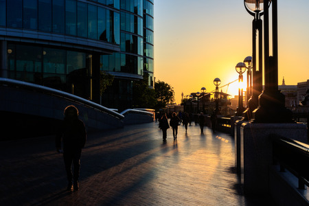 atmospheric: Golden sunset forms atmospheric silhouette of people walking on Thames sidewalk in London Stock Photo