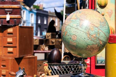 Vintage Globe weergegeven buiten een antiekwinkel op Portobello Road Market in Notting Hill