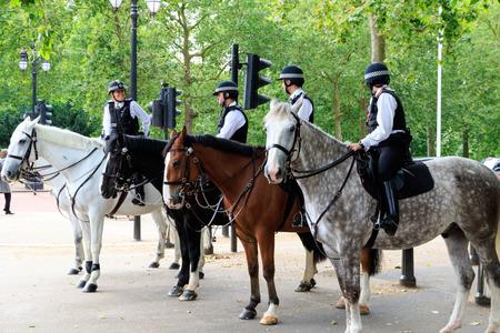 policewomen: London, UK - July 15, 2016 - Mounted Police officers patrol on London streets