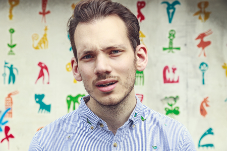 aggravated: Portrait of a aggravated young man standing against a colourful funky background Stock Photo