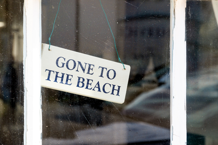 beach window: GONE TO THE BEACH wooden sign hung on window