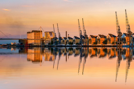 Royal Victoria Dock in London at sunset with dockside cranes and waterfront terraced houses