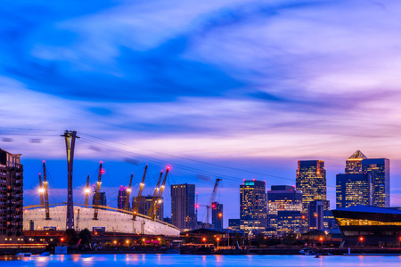 Royal Victoria Dock in London at sunset with illuminated cityscape including Canary Wharf