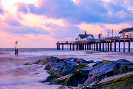 groynes: Sunrise at Southwold Pier with stone groynes, UK