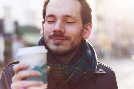 smiley: Scarfed man enjoying warm beverage on a sunny winter day Stock Photo