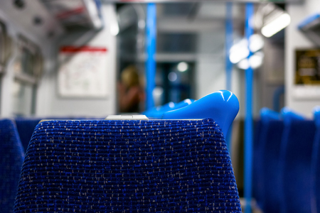 Empty seats in a train carriage with a passenger in the background Stock Photo