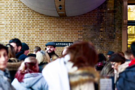 trolly: London, UK - February 28, 2017 - Platform 9 34 from Harry Potter at Kings Cross station seen through queuing crowd