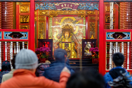 Mazu statue, a Chinese sea goddess, seen through a crowd of prayers at Lungshan Temple of Manka in Taiwan Stock Photo