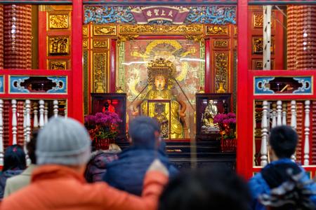 Statua di Mazu, una divinità del mare cinese, vista attraverso una folla di preghiere al Tempio di Lungshan di Manka a Taiwan Archivio Fotografico - 83206505