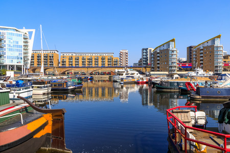 Boats moored at Limehouse Basin Marina in London with DLR passing in the background Stock Photo
