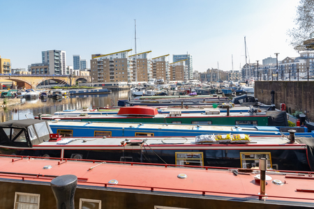 Boats and yachts moored at Limehouse Basin Marina in London with flats in the background