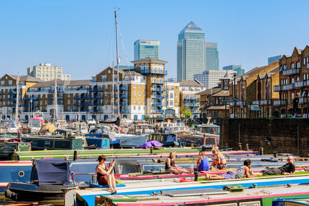 London, UK - April 8, 2017 - People sunbathing on the boats moored at Limehouse Basin with Canary Wharf in the background