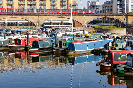 London, UK - April 8, 2017 - Boats and yacht moored at Limehouse Basin Marina with Docklands Light Railway passing by in the background 에디토리얼