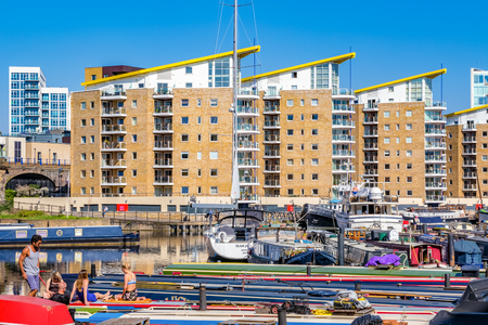 London, UK - April 8, 2017 - People sunbathing on the boats moored at Limehouse Basin with flats in the background 에디토리얼