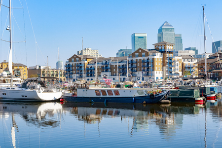 Boats and yachts moored at Limehouse Basin Marina in London with Canary Wharf in the background