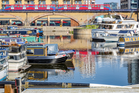 Boats and yachts moored at Limehouse Basin Marina in London with a train passing by in the background 에디토리얼