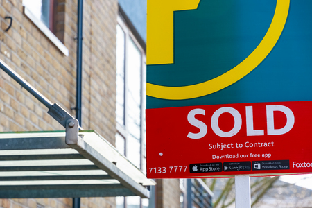 real estate sold: London, UK - March 27, 2017 - Estate agency sold sign outside a English townhouse