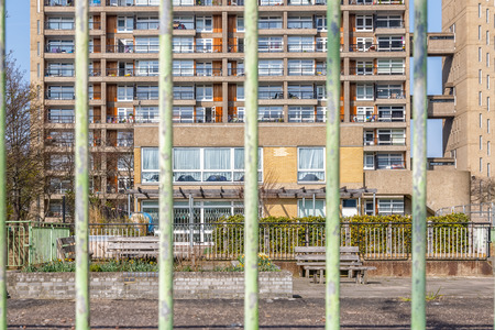 Council housing block in East London seen through bar fence for concept use