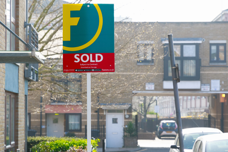 London, UK - March 27, 2017 - Estate agency sold sign outside a English townhouse