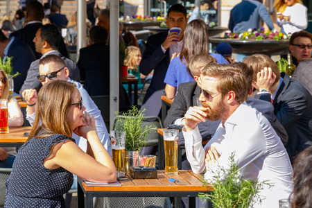 socialise: London, UK - May 10, 2017 - Young businessman and businesswomen drinking at a packed outdoor bar in Canary Wharf on a sunny day