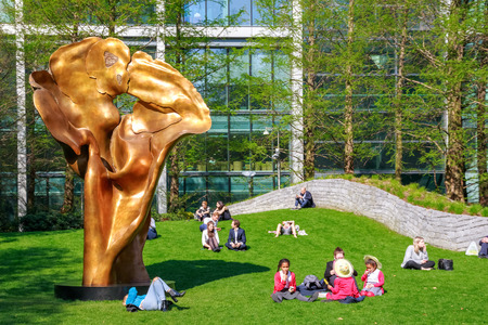 London, UK - May 10, 2017 - Fortuna, a bronze sculpture by Helaine Blumenfeld in Jubilee Park, Canary Wharf, where people are sitting and relaxing on the green grass during a sunny day